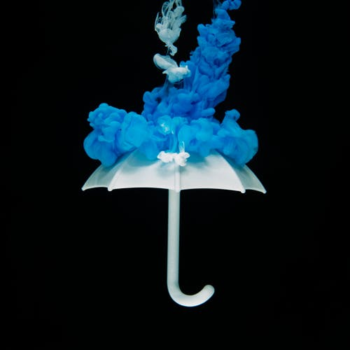 website design artistic photo of a white umbrella with blue smoke ontop